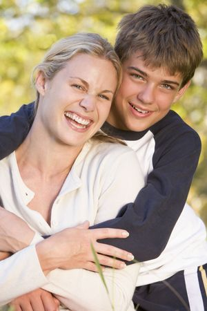 Woman and young boy embracing outdoors and smiling photo