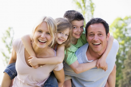 Couple giving two young children piggyback rides smiling photo