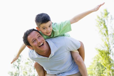 father and son: Man giving young boy piggyback ride outdoors smiling Stock Photo