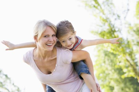 Woman giving young girl piggyback ride outdoors smiling photo