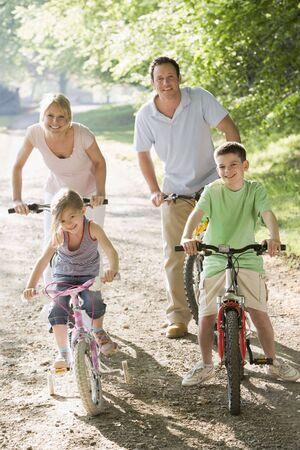 Family on bikes on path smiling photo