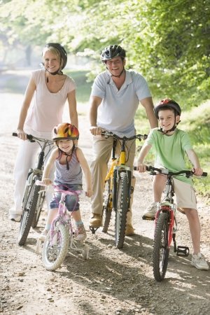 Family sitting on bikes on path smiling photo