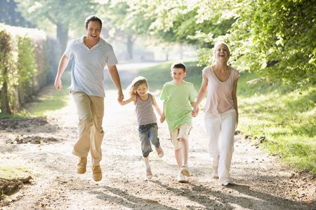 walk in the park: Family running outdoors holding hands and smiling