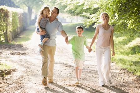 Familia caminar al aire libre la celebración de las manos y sonriendo