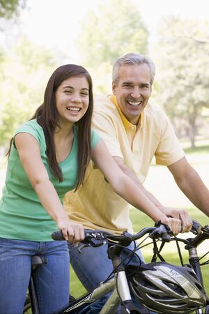 dad daughter: Man and girl on bikes outdoors smiling