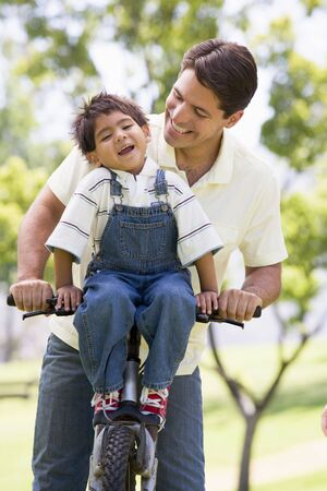 latin kids: Man and young boy on a bike outdoors smiling