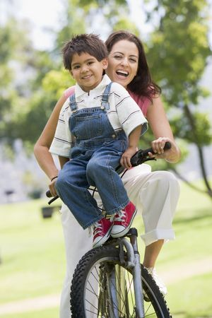 generation x: Woman and young boy on a bike outdoors smiling