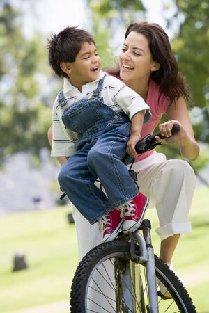 Woman and young boy on a bike outdoors smiling photo