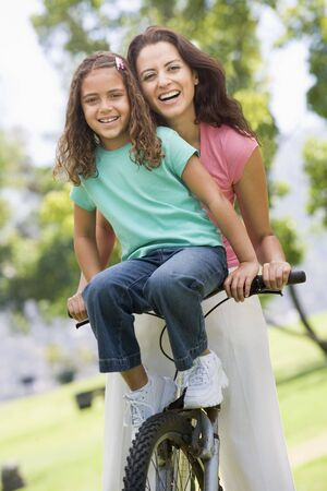 Woman and young girl on a bike outdoors smiling photo