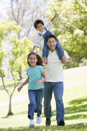 shoulder ride: Man with two young children running outdoors smiling