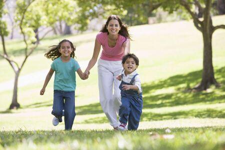 Mujer con dos niños pequeños corriendo sonriente al aire libre