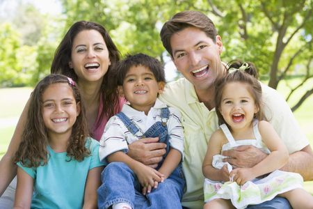 countryside loving: Family sitting outdoors smiling