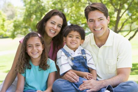 latin family: Family sitting outdoors smiling