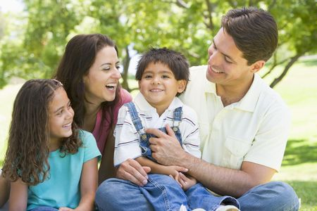 generation x: Family sitting outdoors smiling