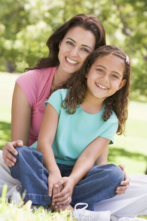 Woman and young girl sitting outdoors smiling photo