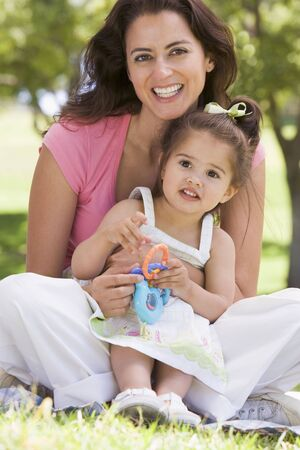 Woman and young girl sitting outdoors with toy smiling photo