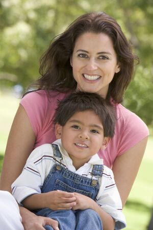countryside loving: Woman and young boy sitting outdoors smiling