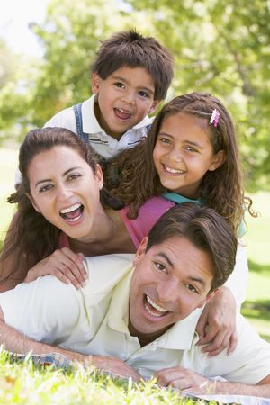 countryside loving: Family lying outdoors smiling