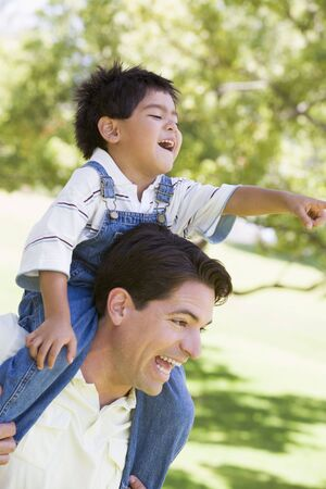 shoulder ride: Man giving young boy shoulder ride outdoors smiling