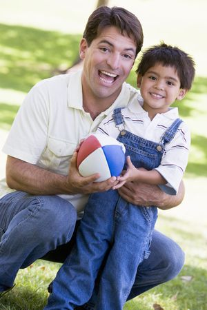Man and young boy outdoors with football smiling Stock Photo - 3475509