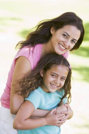 Woman and young girl outdoors embracing and smiling photo