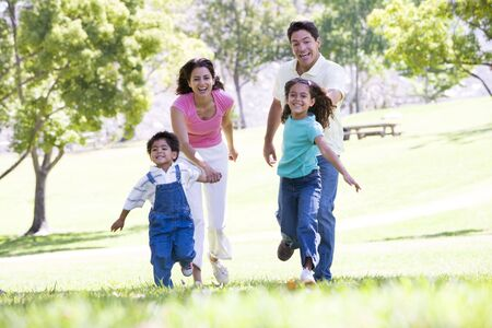 Family running outdoors holding hands and smiling photo