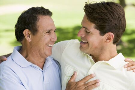 Two men standing outdoors bonding and smiling photo
