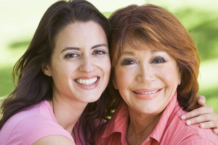 Two women standing outdoors smiling photo