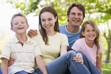 Family sitting outdoors smiling Stock Photo - 3472731