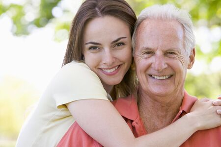 family fun day: Man and woman outdoors embracing and smiling Stock Photo