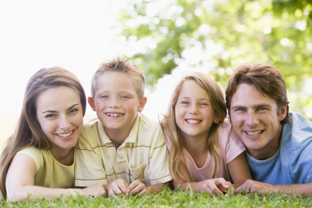 Family lying outdoors smiling Stock Photo - 3471619