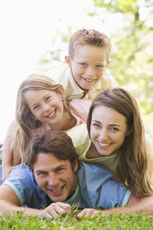 Family lying outdoors smiling Stock Photo - 3474936