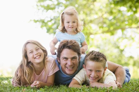 Family lying outdoors smiling Stock Photo - 3461095