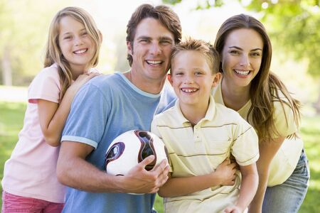 female soccer: Family standing outdoors holding volleyball smiling