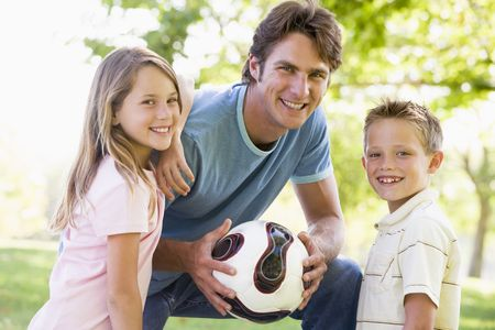 Man and two young children outdoors holding volleyball and smiling photo