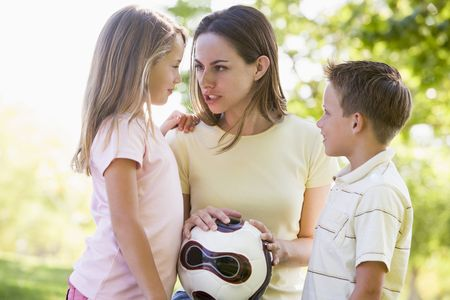 Woman and two young children outdoors holding volleyball and smiling photo