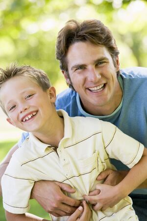 generation x: Man and young boy outdoors embracing and smiling