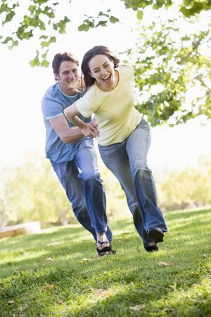 Couple running outdoors holding hands and smiling photo