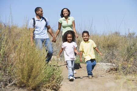 woman hiking: Family walking on path holding hands and smiling