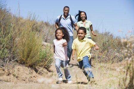 men exercising: Familia ejecuta en camino sonriendo Foto de archivo