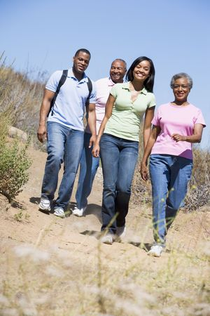 exercising: Two couples walking on path smiling Stock Photo