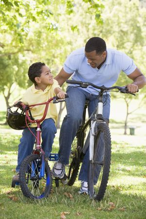Man and young boy on bikes outdoors smiling photo