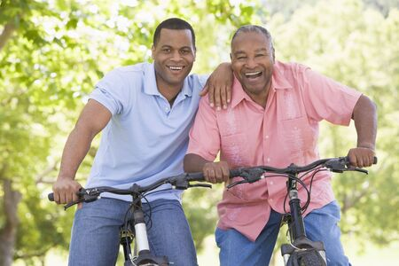 Two men on bikes outdoors smiling photo