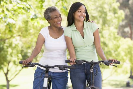 african mother: Two women on bikes outdoors smiling Stock Photo