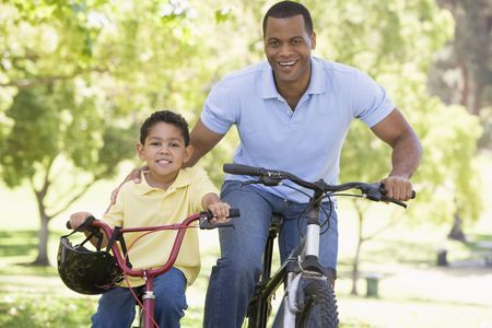 riding: Man and young boy on bikes outdoors smiling