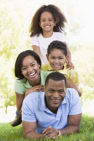 Family lying outdoors smiling Stock Photo - 3472718