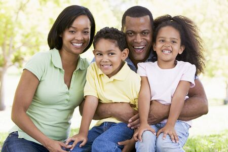 Family sitting outdoors smiling Stock Photo - 3475307