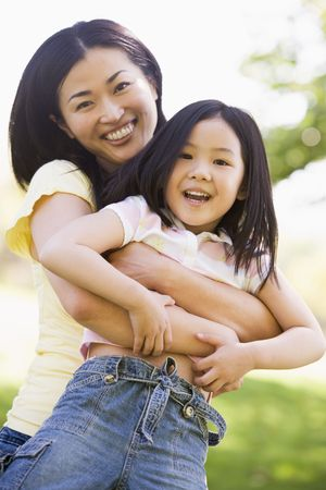 countryside loving: Woman and young girl outdoors embracing and smiling