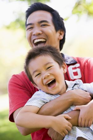 Man and young boy outdoors embracing and smiling photo