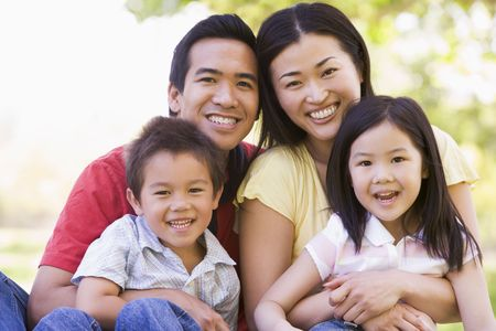 happy asian family: Family sitting outdoors smiling